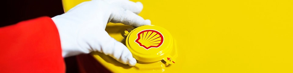 A Shell expert adjusts the lid of a barrel of lubricant displaying the Shell logo