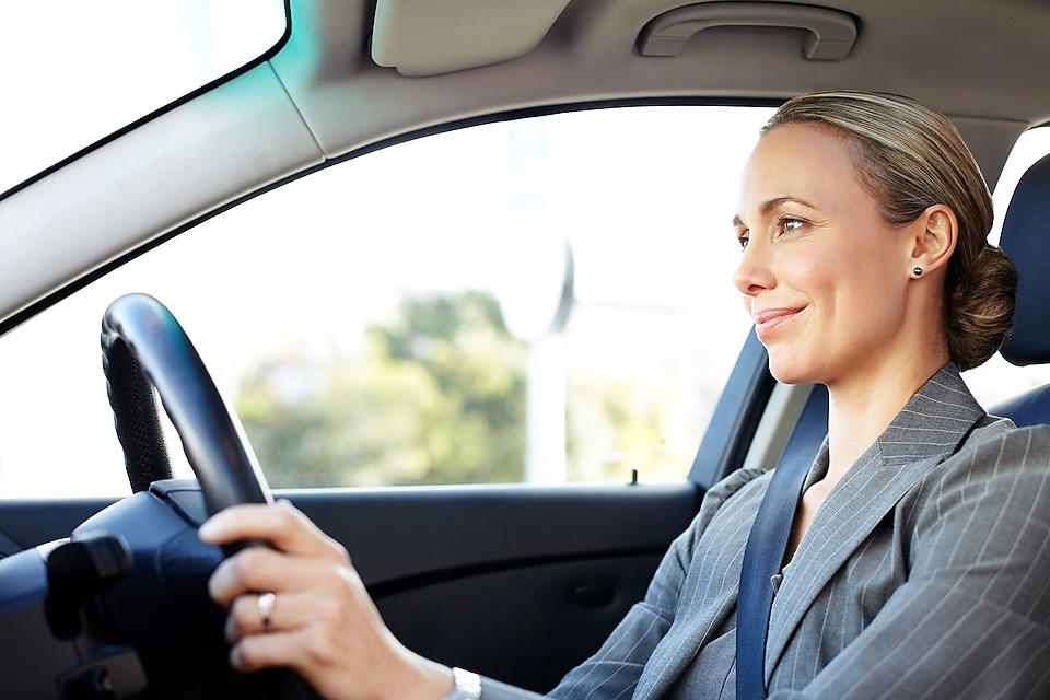 Beautiful female professional smiling while driving car.