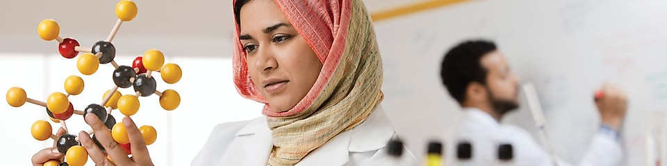 Mixed race scientist in hijab looking at molecule model