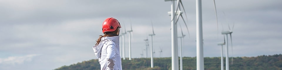 A female Shell employee standing in front of a wind turbine.