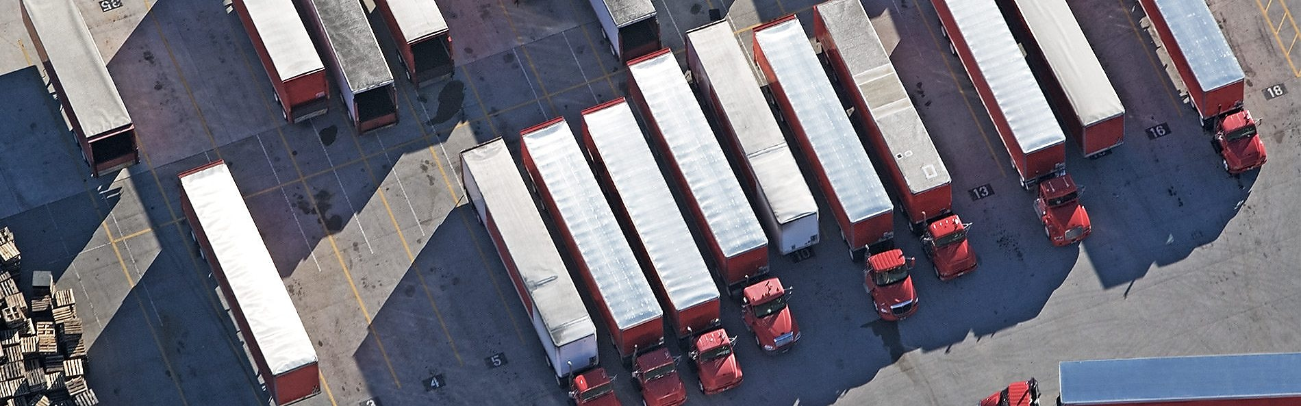 A series of red lorries parked in a row